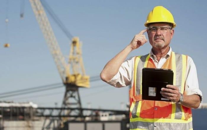 l'image représente un ingénieur sur un chantier qui utilise les nouvelles technologies innovante comme des lunettes intelligente et une tablette, l'ingénieur respecte les règles de sécurité du chantier en ayant un casque et un gilet fluorescent