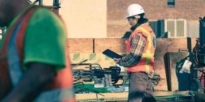 l'image représente un ingénieur sur un chantier qui utilise les nouvelles technologies innovante comme une tablette, l'ingénieur respecte les règles de sécurité du chantier en ayant un casque et un gilet fluorescent