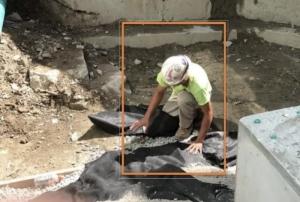 une photo qui montre un ouvrier qui travail à genoux et qui met en place un revêtement d'imperméabilisation