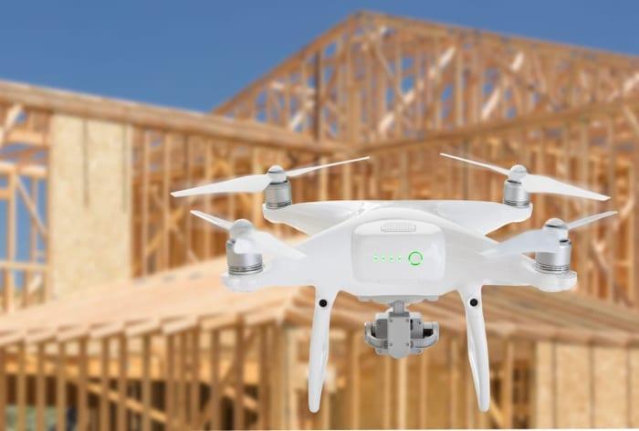 image d'un drone qui vol en dessus du_ chantier pour prévenir les accidents