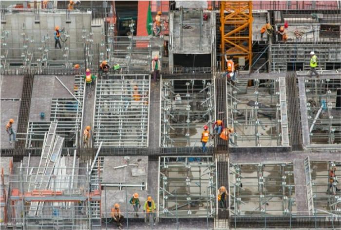 image qui montre des ouvriers qui travaillent sur la ligature de l'armature de la dalle