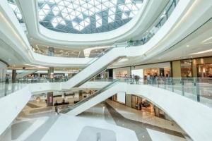 l'image montre le hall intérieur du centre commercial de trois étages, les étages sont reliés par des escalators, chaque étages est en forme circulaire avec les boutiques qui expose leur produits, le Hall est illuminer des rayon du soleil grâce à une imposante toiture vitrée, le tous préfinis par un sol en marbré de couleur blanc crème.