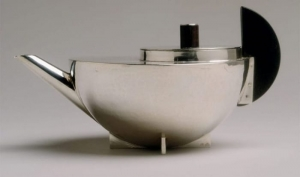 image qui représente la théière et passe thé de 1924 en une forme géométrique et sculpturale et des matériaux d'argent et ébène, bien que jamais produite en série, la théière reflète l'influence du Bauhaus