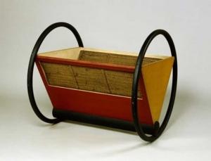 l image motre le berceau, conçu par Peter Keler lors de son passage au Bauhaus, est une icône du design. Elle situe parfaitement la créativité de l'école où les idées fonctionnalistes commencent à être appliquées dans la conception de meubles. D'ailleurs on perçoit très clairement l'influence du mouvement De Stijl sur le Bauhaus à cette époque. D'après les témoignages de l'époque dont on dispose, Keler aurait conçu ce berceau d'après les formes et les théories de la couleur issues du cours de Kandinsky. A noter que cette version est une interprétation du modèle de 1922, car le concept de design de meubles en tubes d'acier n'a pas encore été inventé ( il ne le fut qu'avec le fauteuil Wassily en 1925). A l'origine, les cerceaux étaient en acier plat et la laque bleue était d'une pigmentation plus intense.