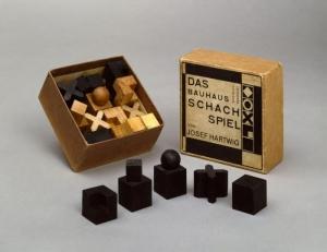 l'image represente le jeu d'échecs de Josef Hartwig, maître artisan de l'atelier de sculpture à l'école du Bauhaus de Weimar, créé vers 1923, ce jeu d'échecs dont les pièces en bois sont totalement abstraites, du jamais-vu jusque-là. Si pendant des siècles, le jeu était l'imitation de l'affrontement de deux armées, il est devenu peu à peu de plus en plus abstrait, purement intellectuel. Il n'est plus nécessaire, expliquait Hartwig, de représenter les pièces de manière réaliste. Elles doivent être abstraites et maniables, conformes au sens du jeu. Les formes géométriques symbolisent leurs mouvements sur l'échiquier