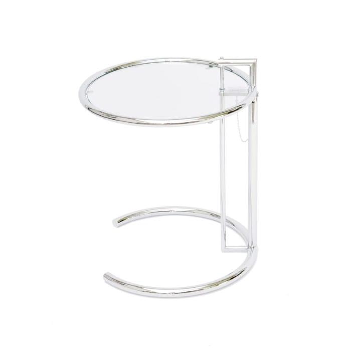 l image représente la table de Eileen Gray (1878-1976) est l'une des personnalités les plus marquantes de l'histoire des arts décoratifs et de l'architecture du XXème siècle. Ses oeuvres, aujourd'hui devenues des classiques de l'Art Déco et du Design, atteignent des prix records dans les ventes aux enchères. E-1027 est une réédition de la table conçue par Eileen Gray en 1927 pour sa villa à Roquebrune. En 1924, en collaboration avec l'architecte roumain Jean Badovici, Eileen Gray commence à travailler sur la maison E-1027. Chargée de son ameublement, elle crée cette table très novatrice pour l'époque. Le luxe cède la place à la simplicité et à une forme utile. Le plateau en verre est réglable en hauteur grâce à un pied coulissant. Eileen Gray est l'une des premières à utiliser des structures tubulaires en acier avec Marcel Breuer, Gerrit Rietveld et Charlotte Perriand. Créée en 1927, cette table étonne par sa modernité : elle pourrait être une création d'aujourd'hui. Rééditée comme « classique du Design » depuis près de 40 ans, c'est un meuble ajustable, utile et adapté à l'espace moderne.