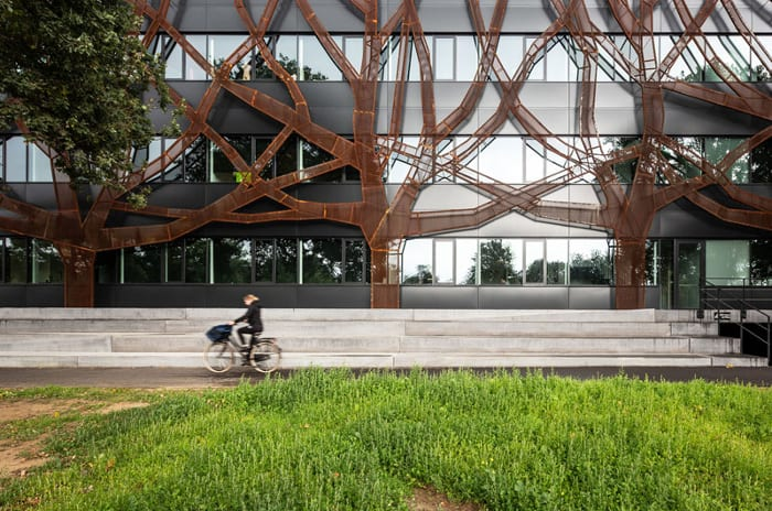 l'image représente l'école passive et la façade ou sont installées des bandes de verre et des panneaux d'aluminium noir qui lui confèrent un aspect élégant et moderne.par dessus il y a une deuxième peau d'acier en corten perforée, rappelant la forme d'un chêne, dans le but de le protéger du rayonnement solaire excessif.