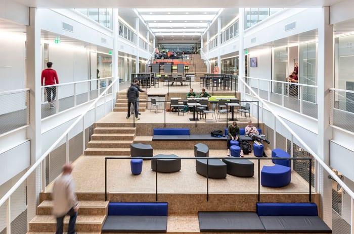 l'image montre l'école passive let ses espaces intérieurs du Graafschap College de Doetinchem, l espaces se subdivise en 2 long corridors qui donne accès au classe, et au milieu de ces 2 corridors des espaces de relax sur plusieurs niveaux qui permette aux étudiants d'échanger et de partager leur considérations