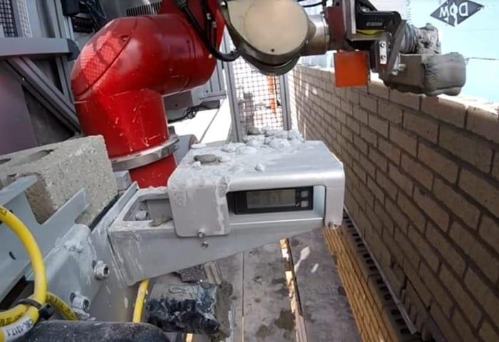 L'image du bras robot Sam de Construction Robotics en action qui applique une couche de mortier puis les empile en suivant un guidage laser.