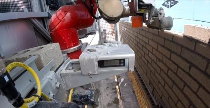 L'image montre Sam un robot conçu par la société Construction Robotics, Sam est un robot capable d'effectuer le volume de travail de six ouvriers. Le principe : depuis un engin mobile, un bras articulé récupère les briques, leur applique une couche de mortier puis les empile en suivant un guidage laser.