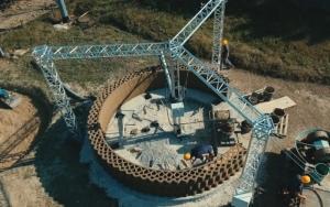 L'image représente une construction d'une maison, sa particularité est que pour la construction on utilise une imprimante Crane Wasp 3D qui construit les murs d' une hauteur de colonne 405m, une longueur de bras de 330m , cette imprimante est fixée à l'aide de 3 pieds, pour la constructions on utilisent des matériaux ont été mélangés à l'aide d'un broyeur humide, ce qui a rendu le mélange homogène et utilisable.