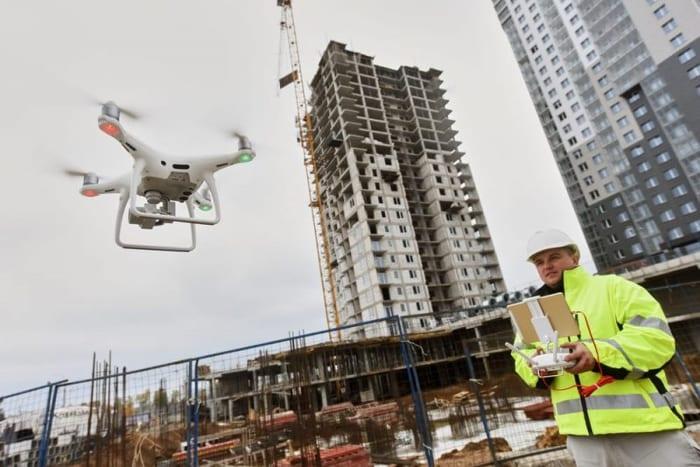 L'image représente un expert qui pilote un drone pour faire des relever sur le chantier et pour le contrôle du chantiers, voilà les nouvelles technologies