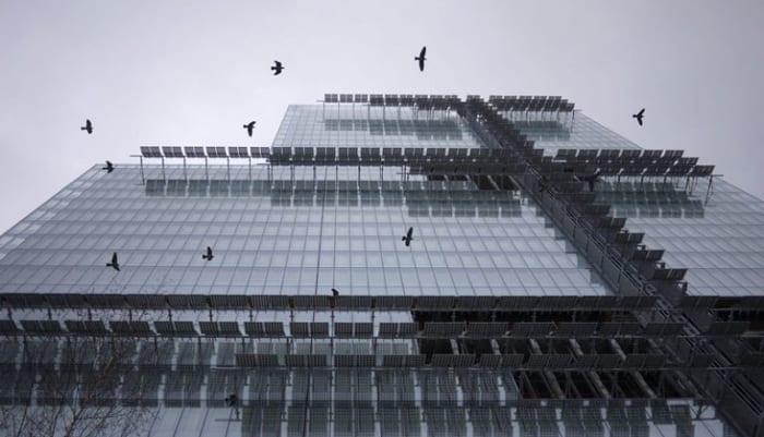 L'image est une vue depuis le bas vers le haut du Palais de Justice de Paris entièrement réalisé en vitre et avec un projet en méthodologie BIM