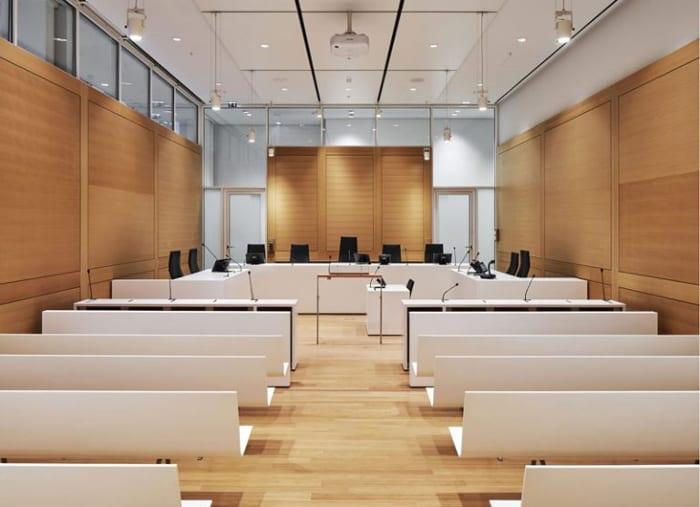 L'image représente une des salle d'audience avec ses bancs blanc et ses parois en bois le tout couronner d'un plafond blanc, ce projets réaliser en BIM