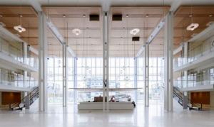 L'image représente l'entrée principale des Pas Perdus avec ses baies vitrées et ses longues lampes suspendues au plafond ainsi que ses escaliers mécaniques au deux extrémités de l'atrium, ce projets réaliser en BIM
