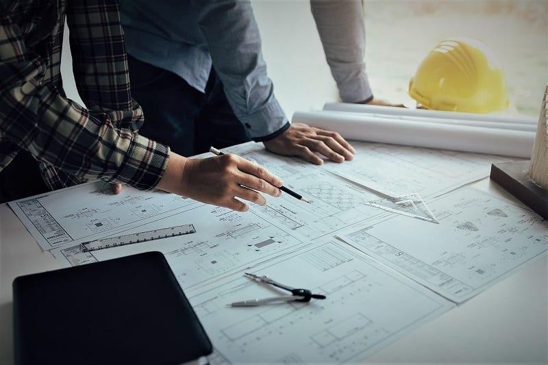 L'image illustre deux ingénieurs travaillant avec les plans et discutant du projet ensemble lors de la réunion au bureau, dans l'article présentation du projet d'architecture, Edificius logiciel de conception architecturale 3D BIM