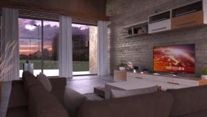 L'image est un rendu d'intérieur d'un salon avec un mur en effet brique sous lequel un meuble bas pour la télévision et un canapé en angle de couleur brun avec une baie vitrée, issu du logiciel Edificius de conception architecturale 3D BIM.