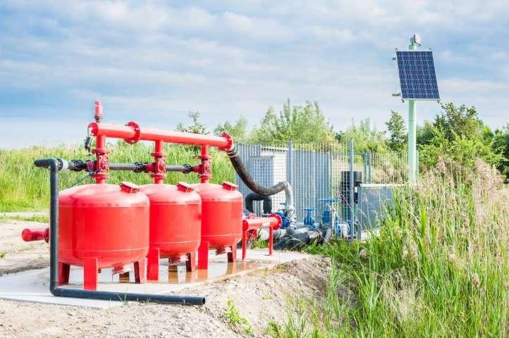 Une installation d'un système de pompage mis en pratique sur le champ, il y a trois reversoirs et le système de pompage protéger par un grillage.