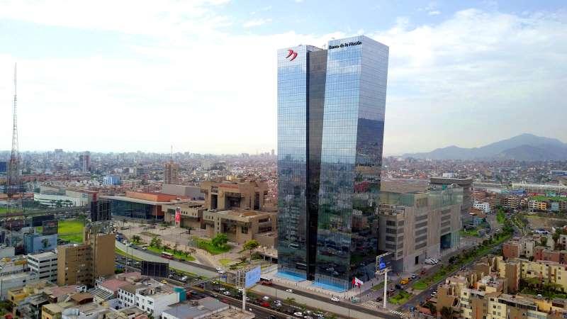 Une photo de la tour de la Banque De La Nation du Pérou, en haut de la tour une enseigne à deux virgules qui symbolises le logo de la banque