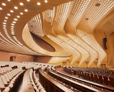 L'auditorium à un plafond en forme de vague de couleur bois en dégradée il peu accueillir 2100 personne assises.