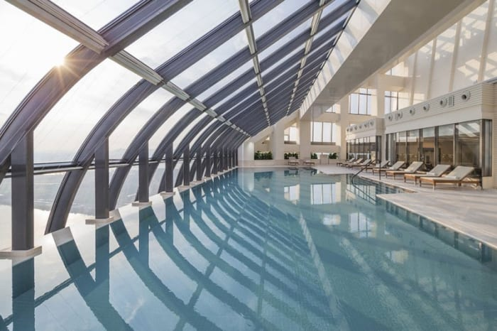 Un rendu intérieure de l'espace de la piscine, avec une charpente métallique et de grande fenêtres qui font rentrés la lumière du jour