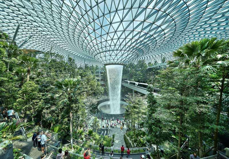 Le rendu est une immense cascade immergée dans une serre de verre qui abrite un jardin tropical de l'aéroport de Singapour