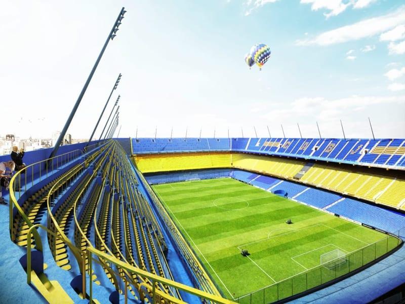 Rendu du stade la Bombonera une fois terminé, le stade alterne avec des couleurs jaunes et bleus et il y a un dirigeable qui survole la pelouse verte du stade.