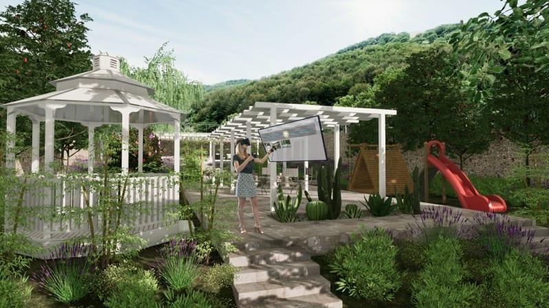 A imagem mostra uma menina andando dentro de um render de um jardim. A menina está usando óculos de realidade virtual e está alterando os objetos presentes no render com um controlador