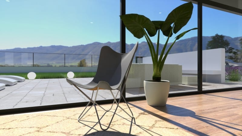 A imagem mostra uma cadeira cinza perto de uma planta e em frente de uma parede de vidro. A cadeira é iluminada pela luz do sol. A imagem é uma renderização produzida no Edificius